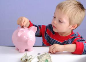 Kid putting money into a piggy bank