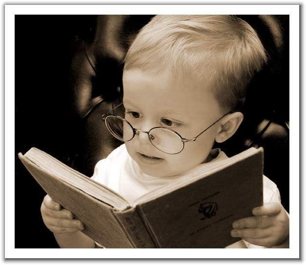 A baby reading a book with glasses.